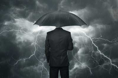 man in umbrella facing storm