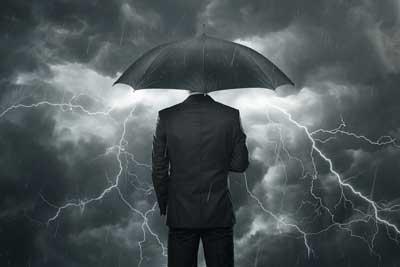 man in umbrella facing storm